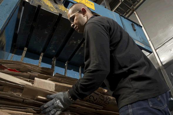 Trabajador compacta cartón en la planta de Ecorecyclar